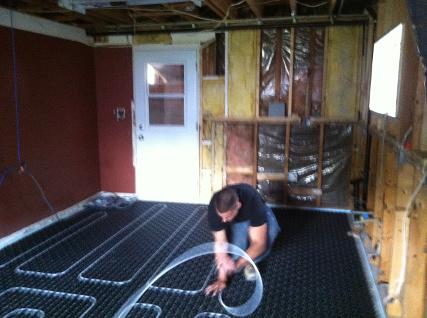 Plumbing apprentice installing floor radiant heat piping on an Uponor Fast Track application.
